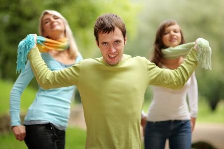 playboy: Jonge man spelen met twee meisjes. Ondiepe DOF.