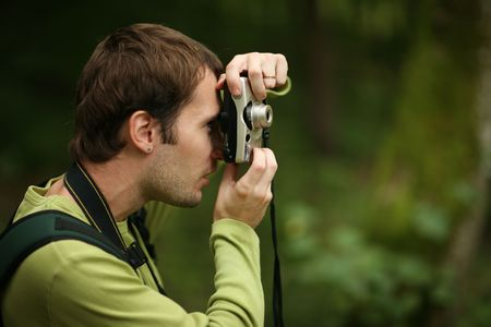 Photographer shooting with compact camera in forest. Shallow DOF. Stock Photo - 5947177