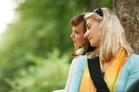 moment: Two beautiful young women relaxing in forest. Shallow DOF.