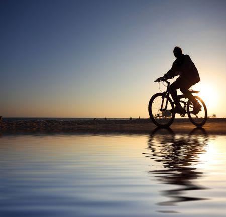 reflexion: Silueta de motociclista montando a lo largo de la playa al atardecer