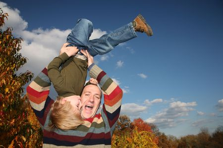 Happy father lifting son upside down over blue sky photo
