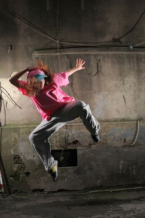 danza contemporanea: Joven bailar�n saltando sobre una calle junto a la antigua muralla grunge Foto de archivo