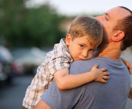 肩の周りの小さな少年ハグ ハグ父