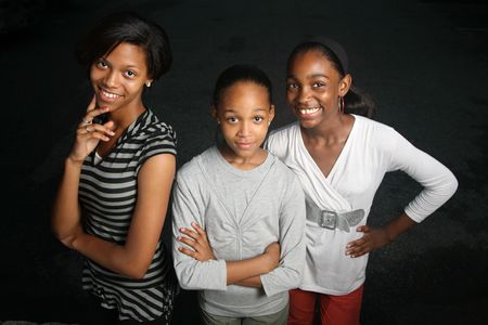Happy African American family. Three teenage sisters together looking at camera, smiling.
