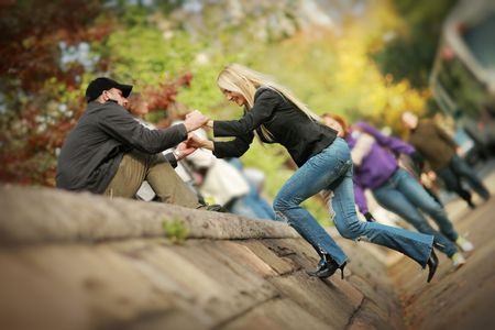 trespasser: Man helping woman to climb wall in park. Shallow DOF.