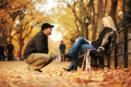 adult dating: Man talking to hot blond woman in autumn park. Shallow DOF. Stock Photo