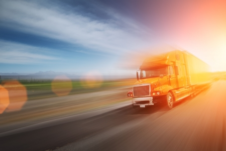 dynamic motion: Truck speeding on freeway at sunset. Blurred motion.