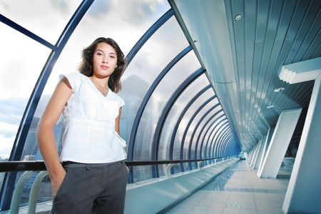 Confident young businesswoman in futuristic interior.