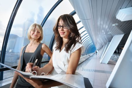 Two businesswomen looking into papers in futuristic interior