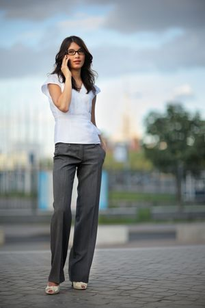 long pants: Beautiful woman talking on mobile phone in city. Shallow DOF.