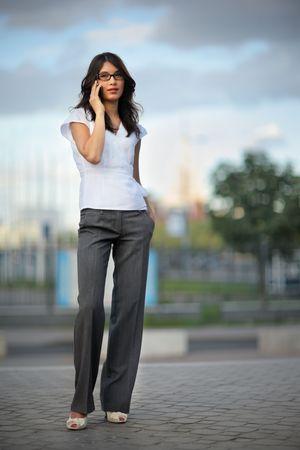calling: Hermosa mujer hablando por tel�fono m�vil en la ciudad. GDL superficial.