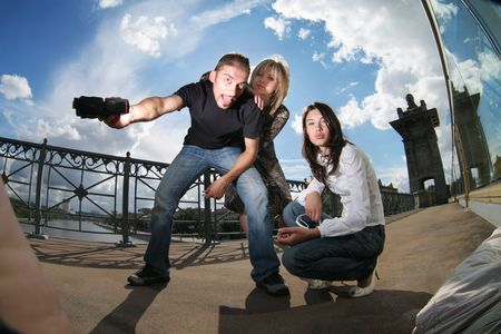 Wide angle portrait of photographer with two beautiful models having fun at photoshoot.