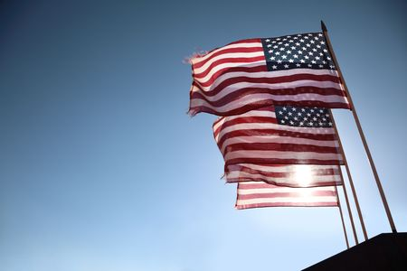 backlit: Four American flags waving over blue sky