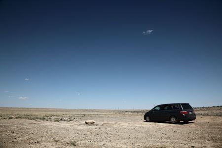 Car in desert under blue sky photo