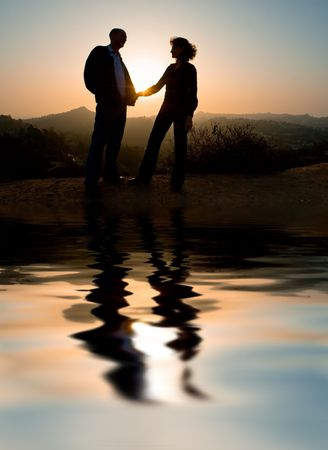 Couple silhouette outdoors, beautiful sunset behind.