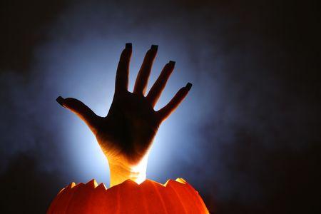 Human hand  raising from glowing pumpkin lantern Stock Photo - 5997697