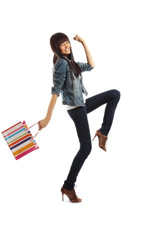 stepping: Happy young woman going shopping enthusiastically, isolated over white background.
