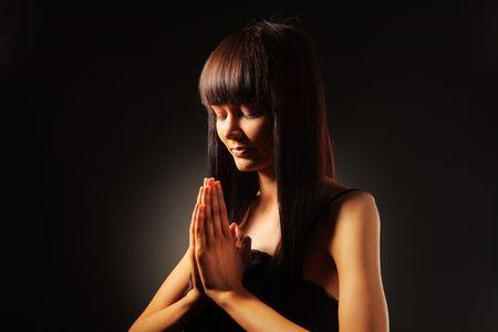 medium close up: Beautiful young woman praying over black background.
