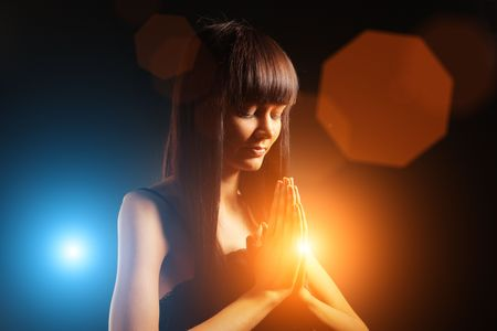 shining light: Beautiful young woman praying over black background.