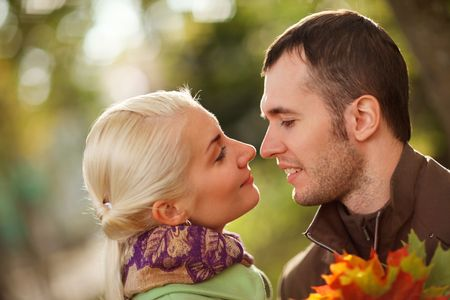 Young couple in love outdoors in park, close-up, shallow DOF. photo