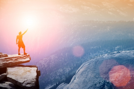 Man die op de top van een klif met arm verhoogd