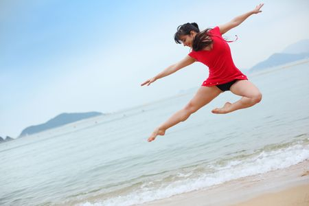 contemporary: Beautiful young woman dancing on beach