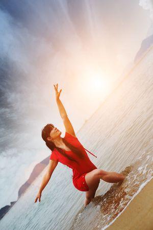 Beautiful young woman dancing on beach photo