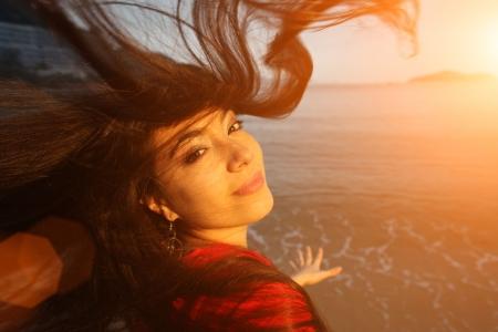カメラで見る夕日のビーチで髪を飛行を持つ若い美しい女性。 写真素材