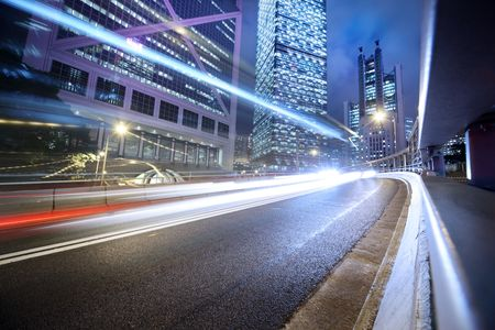 future city: Fast moving cars lights blurred over modern city background