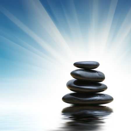 reflects: Stack of zen stones reflects in blue water surface Stock Photo
