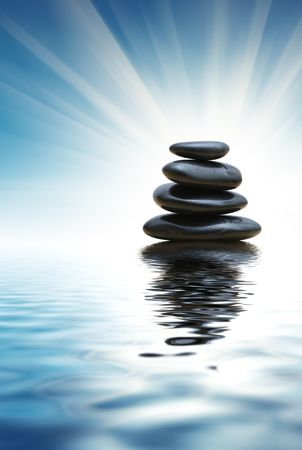 Stack of zen stones reflects in blue water surface Foto de archivo