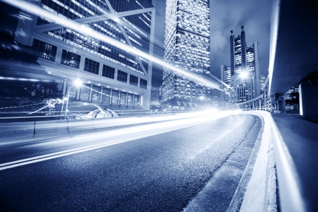 Fast moving cars lights blurred over modern city background photo