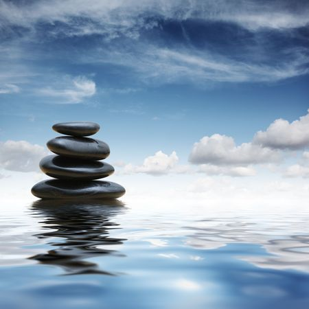 Stack of black zen pebble stones reflecting in water over blue sky background Stock Photo