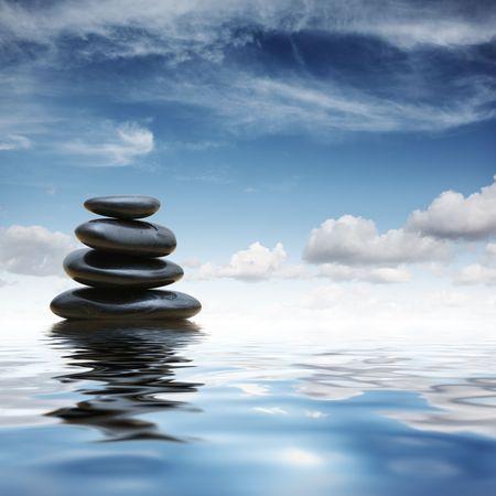 Stack of black zen pebble stones reflecting in water over blue sky background Banco de Imagens