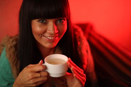 Close-up portrait of beautiful young woman drinking hot ginger tea with lemon. Shallow DOF,. Stock Photo - 6462419