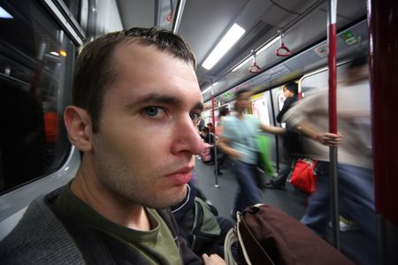 Close-up portrait of young man in subway car. Ultra-wide angle. photo