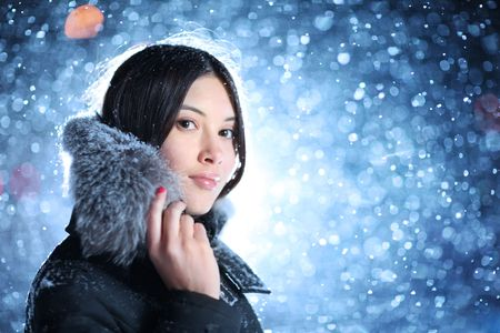 Portrait of beautiful young woman over falling snow background photo