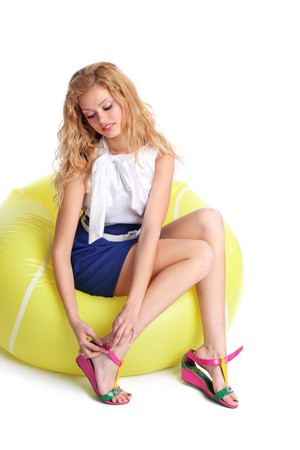 Young woman in yellow inflatable chair putting on summer shoes. photo