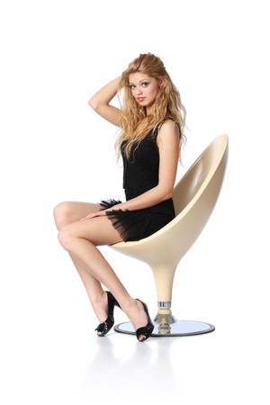 Beautiful young blond woman sitting in white designer chair