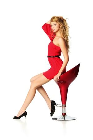 Mooie jonge vrouw in het rood zittend op bar stoel, geïsoleerd op witte achtergrond.