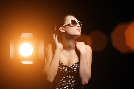 Studio portrait of beautiful woman with bright spotlight over black background photo