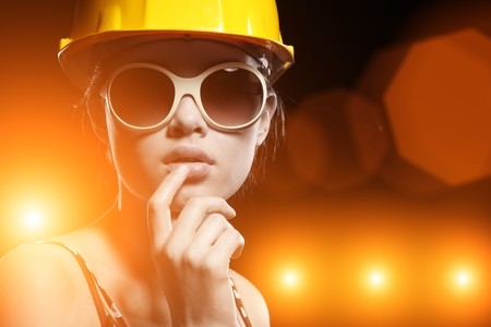 Portrait of fashionable female construction worker over glowing lights background photo