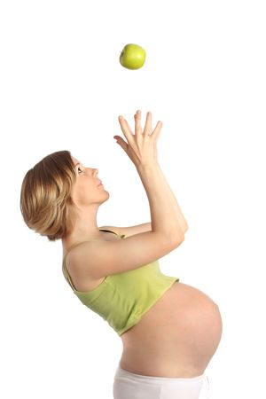 Pregnant woman catching a green apple photo