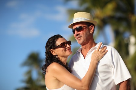 Happy mature adult couple enjoying vacation at tropical resort. Close-up, shallow DOF. photo