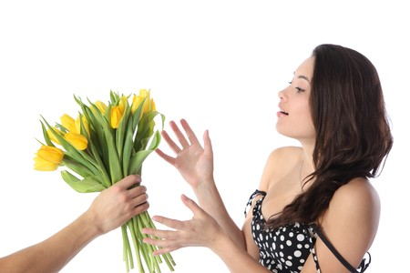 Beautiful young brunette woman receiving gift bouquet of fresh yellow tulip flowers. Isolated over white background. photo
