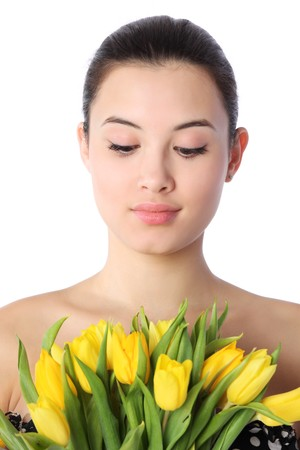 head down: Close-up portrait of beautiful young woman with yellow tulips, isolated over white background