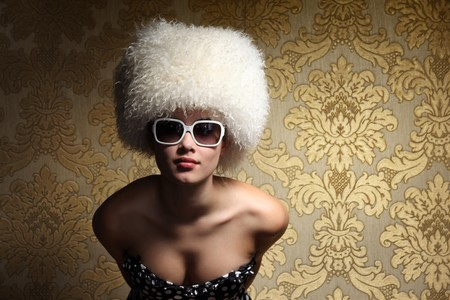 Portrait of beautiful sexy young woman in white fur hat posing over golden vintage floral wallpaper background. photo