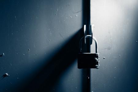 padlocked: Padlock lock on metal gates background. Stock Photo