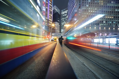 Fast moving bus lights blurred over modern city background photo