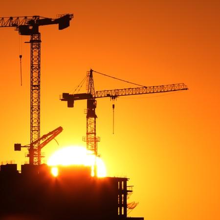 Industrie bouw kranen en gebouw silhouetten over zon bij zons opgang.